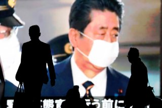 Passersby are silhouetted in front of a giant screen reporting Japan's Prime Minister Shinzo Abe and Japan's response to the coronavirus disease (COVID-19) outbreak in Tokyo, Japan April 7, 2020. REUTERS/Issei Kato