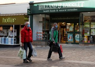 People wearing protective face masks are seen outside a Holland & Barrett store in Durham, as the spread of the coronavirus disease (COVID-19) continues, Durham, Britain, April 8, 2020. REUTERS/Lee Smith