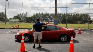A worker controls the traffic as people in cars wait in line to pick up receiving an unemployment forms, as the outbreak of coronavirus disease (COVID-19) continues, in Hialeah, Florida, U.S., April 8, 2020. REUTERS/Marco Bello