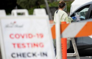 A health worker in protective gear hands out a self-testing kit in a parking lot of Rose Bowl Stadium during the global outbreak of the coronavirus disease (COVID-19), in Pasadena, California, U.S., April 8, 2020. REUTERS/Mario Anzuoni