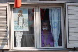 People observe from their window a crucifix displayed outside the Santa Maria della Sanita church during Good Friday, as Italy remains on lockdown during the Easter period to try and contain the spread of coronavirus disease (COVID-19), in Naples, Italy A