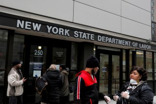 People gather at the entrance for the New York State Department of Labor offices, which closed to the public due to the coronavirus disease (COVID-19) outbreak in the Brooklyn borough of New York City, U.S., March 20, 2020. REUTERS/Andrew Kelly