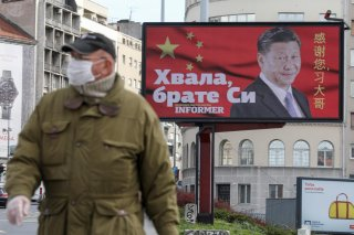 A man wearing a protective mask passes by a billboard depicting Chinese President Xi Jinping as the spread of the coronavirus disease (COVID-19) continues in Belgrade, Serbia, April 1, 2020. The text on the billboard reads