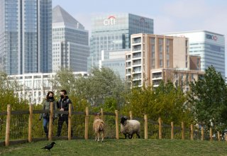 People wearing protective face masks are seen at Mudchute Park and Farm near the Canary Wharf financial district, as the spread of the coronavirus disease (COVID-19) continues, London, Britain, April 13, 2020. REUTERS/John Sibley