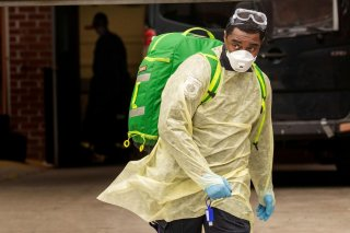 An Emergency Medical Technician (EMT) wearing personal protective equipment (PPE) walks out of the Cobble Hill Health Center nursing home during the ongoing outbreak of the coronavirus disease (COVID-19) in the Brooklyn borough of New York, U.S., April 17