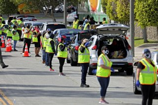 Volunteers control traffic flow as households receive boxes of food at a drive-thru food distribution site from the Los Angeles Regional Food Bank and Los Angeles County Federation of Labor as authorities encourage social distancing to prevent the spread