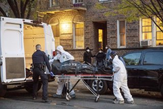 An officer from the New York Police Department helps workers carry a body out of a house amid the coronavirus disease (COVID-19) outbreak, in the Brooklyn borough of New York City, U.S., April 20, 2020. REUTERS/Lucas Jackson