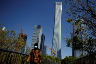 "A woman wearing a protective mask walks near the Central Business District on a ""blue sky day"