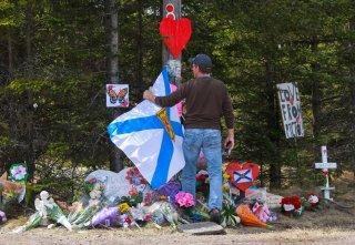 A man adjusts the Nova Scotia flag in front of the makeshift memorial, made in the memory for the victims of Sunday's mass shooting in Portapique, Nova Scotia, Canada April 23, 2020. REUTERS/Tim Krochak