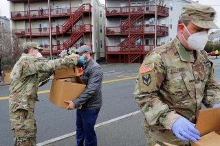 Members of the 101st Engineer Battalion of the Massachusetts Army National Guard distribute free groceries at a pop-up food pantry amid the coronavirus disease (COVID-19) outbreak in Chelsea, Massachusetts, U.S., April 24, 2020. REUTERS/Brian Snyder