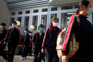 Students wearing face masks leave a school in Beijing, China as senior high school students in the Chinese capital returned to campus following the coronavirus disease (COVID-19) outbreak, April 27, 2020. REUTERS/Thomas Peter