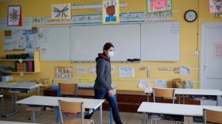 Teacher Nancie Toullec, wearing a protective face mask, walks in a deserted classroom installed to maintain social distancing in a private school open to children of health workers and workers on the coronavirus frontline in Saint-Sebastien-sur-Loire near