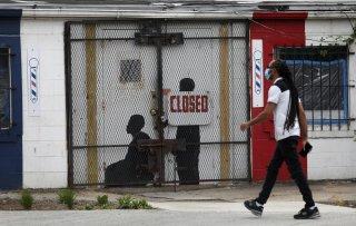 A pedestrian walks past a closed barber shop in Ward 7 as the coronavirus disease (COVID-19) outbreak continues in Washington, U.S., May 8, 2020. REUTERS/Leah Millis