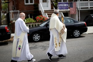 Deacons Paul Norman (R) and Robert Lavanco of Our Lady of Hope Catholic Church lead a procession called the Blessed Sacrament, to bring blessings to worshippers outside their homes while their church sanctuary is closed to them in the Queens borough of Ne