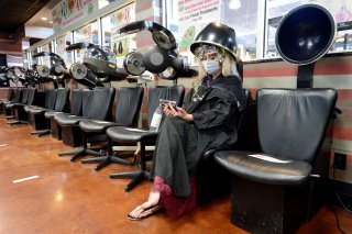 Jessica King sits under a dryer at Three-13 Salon, Spa and Boutique, during the phased reopening of businesses and restaurants from coronavirus disease (COVID-19) restrictions in the state, in Marietta, Georgia, U.S., April 24, 2020. REUTERS/Bita Honarvar