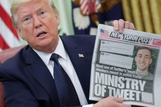 U.S. President Donald Trump holds up a front page of the New York Post as he speaks to reporters while discussing an executive order on social media companies in the Oval Office of the White House in Washington, U.S., May 28, 2020. REUTERS/Jonathan Ernst