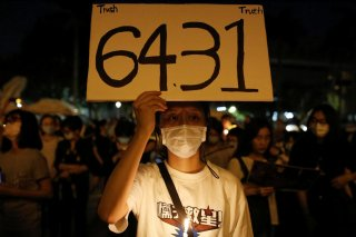A man wearing a protective mask holds a placard at Liberty Square in Taipei to mark the 31st anniversary of the crackdown of pro-democracy protests at Beijing's Tiananmen Square in 1989, Taiwan, June 4, 2020. REUTERS/Ann Wang