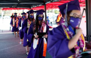 Compton Early College High School graduating students wait after picking up their diplomas in a parking lot during a drive-thru graduating ceremony, during the outbreak of the coronavirus disease (COVID-19) in Compton, California U.S. June 10, 2020. REUTE