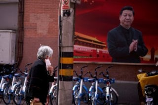 A woman with a protective mask is seen past a portrait of Chinese President Xi Jinping on a street as the country is hit by an outbreak of the coronavirus, in Shanghai, China March 12, 2020. REUTERS/Aly Song