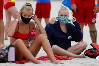 Participants apply their masks after a beach run as San Diego's Junior Lifeguard Program officially reopens with new protocols in place to comply with county health guidelines for coronavirus safety during the outbreak of COVID-19 in San Diego, California
