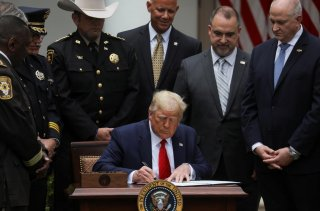 U.S. President Donald Trump signs an executive order on police reform while surrounded by law enforcement leaders during an event in the Rose Garden at the White House in Washington, U.S., June 16, 2020. REUTERS/Leah Millis