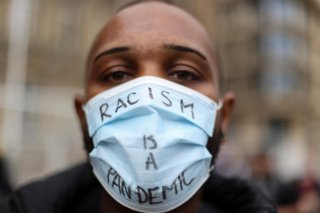 A person wearing a protective face mask attends the Black Lives Matter protest, following the death of George Floyd who died in police custody in Minneapolis, in Birmingham, Britain, June 19, 2020. REUTERS/Carl Recine