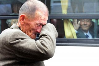 A North Korean man (R) on a bus waves his hand as a South Korean man weeps after a luncheon meeting during inter-Korean temporary family reunions at Mount Kumgang resort October 31, 2010. Kim Ho-Young/Korea Pool via REUTERS