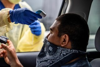 Joe Garcia has his heart rate and temperature checked before getting tested for the coronavirus disease (COVID-19) during its outbreak, in Austin, Texas, U.S., June 28, 2020. REUTERS/Sergio Flores