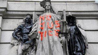 A defaced statue is pictured across from a protest to defund the police in a place they are calling the