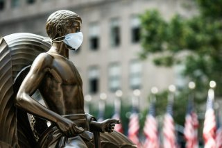 The Mankind Figure of Youth statue at Rockefeller Center in Manhattan is seen adorned with a face mask following the outbreak of the coronavirus disease (COVID-19), in New York City, New York, U.S., July 5, 2020. REUTERS/Jeenah Moon