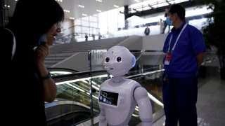 People wearing face masks following the coronavirus disease (COVID-19) outbreak are seen near a robot at the venue for the WorldArtificialIntelligenceConference (WAIC) in Shanghai, China July 9, 2020. REUTERS/Aly Song