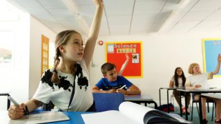 A girl gestures in a classroom at Watlington Primary School during the last day of school, amid the coronavirus disease (COVID-19) outbreak, in Watlington , Britain, July 17, 2020. REUTERS/Eddie Keogh
