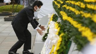 Japan's Prime Minister Shinzo Abe wearing a protective face mask, offers a wreath to the cenotaph for the victims of the 1945 atomic bombing, at Peace Memorial Park in Hiroshima, western Japan, August 6, 2020, on the 75th anniversary of the atomic bombing