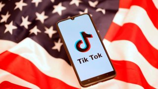 TikToklogo is displayed on the smartphone while standing on the U.S. flag in this illustration picture taken, November 8, 2019. REUTERS/Dado Ruvic