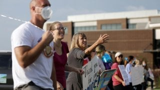 Supporters of the Cherokee County School District's decision to reopen schools to students during the coronavirus disease (COVID-19) pandemic cheer on faculty arriving to the district's headquarters, the Dr. Frank R. Petruzielo Educational Services Facili