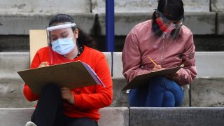 Young people wearing protective face masks and face shields maintain social distancing as a measure to contain the spread of the coronavirus disease (COVID-19) as they take the entrance exam for Mexico's National Autonomous University in the stands of Uni