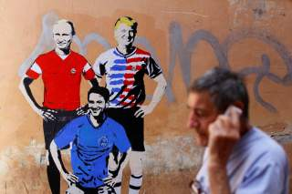 A man walks past a mural signed by