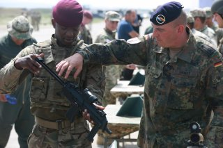 A German soldier with the 291st Infantry Division (right), explains the functions of the MP7-PDW to a British soldier (left) assigned to 2nd Parachute Regiment, Vaziani Airfield, Republic of Georgia, July 30, 2017. U.S. Army/Joseph E. Cannon.