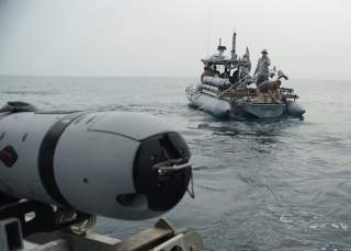 A team of unmanned underwater vehicle operators, attached to Commander, Task Group 56.1, lower a UUV into the water for an underwater survey.