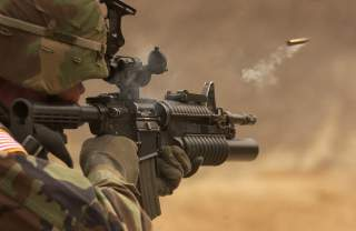 A shell casing flies out with a trail of smoke as U.S. Army Pfc. Michael Freise fires an M-4 rifle during a reflex firing exercise at the Rodriguez Live Fire Complex, Republic of Korea, on March 23, 2005.