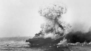 A mushroom cloud rises after a heavy explosion on board the U.S. Navy aircraft carrier USS Lexington (CV-2), 8 May 1942. This is probably the great explosion from the detonation of torpedo warheads stowed in the starboard side of the hangar, aft