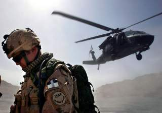 A Canadian soldier from the NATO-led coalition force turns his back away from a dust cloud kicked up by a Blackhawk helicopter taking off from the forward operating base of Ma'sum Ghar, Afghanistan, July 1, 2007. REUTERS/ Finbarr O'Reilly (AFGHANISTAN)