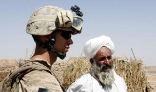 A U.S. Marine from 2nd platoon, F company, 5th batalion, 10th Marines, meets an Afghan villager during a patrol in southern Afghanistan June 28, 2009. After five years coping with the most dangerous province in Iraq, the U.S. Marines have been given their