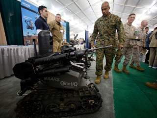 A soldier looks at a MAARS (Modular Advanced Armed Robotic System) robot at the Marine West Military Expo at Camp Pendleton, California February 1, 2012. The expo is one of the year's largest annual display of new military equipment. REUTERS/Mike Blake (U