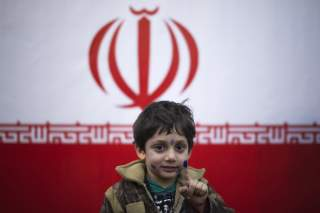A young boy stands in front of Iran's national flag with his ink stained face and finger, symbolizing a voter who already has cast his vote, in a polling station during Iran's parliamentary election in southern Tehran March 2, 2012. REUTERS/Morteza Nikoub