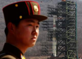 A soldier stands guard in front of the Unha-3 (Milky Way 3) rocket sitting on a launch pad at the West Sea Satellite Launch Site, during a guided media tour by North Korean authorities in the northwest of Pyongyang April 8, 2012. REUTERS/Bobby Yip (NORTH