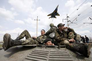 A fighter jet flies above as Ukrainian soldiers sit on an armoured personnel carrier in Kramatorsk, in eastern Ukraine April 16, 2014. Ukrainian government forces and separatist pro-Russian militia staged rival shows of force in eastern Ukraine on Wednesd