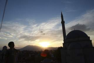 Image:A boy looks at the sky near an orthodox church and a mosque in Prizren, southwest from capital Pristina August 20, 2014.REUTERS/Hazir Reka