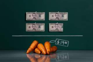 A kilogram (2.2 lbs) of raw carrots as photographed in a studio with an illustrative price tag of $19.05 (US dollars), equivalent to the Bs. 120 (bolivars) that it costs on average to purchase in Caracas at the official exchange rate of 6.3 bolivars per d