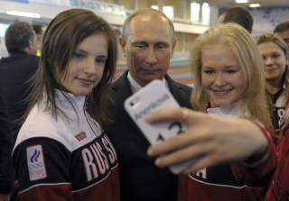 Russian President Vladimir Putin (C) poses for a picture with youths who took part in the Nanjing 2014 Youth Olympic Games, as he visits a local Olympic youth sports school in Cheboksary, October 9, 2014. REUTERS/Alexei Druzhinin/RIA Novosti/Kremlin